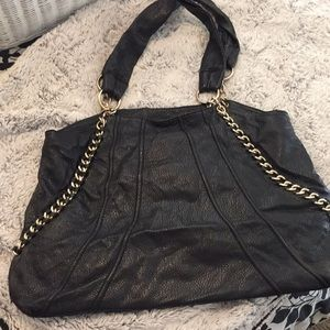 Black purse with gold metal straps